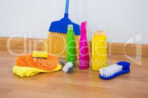 Chemical bottles by brush and sponges with broom on floor