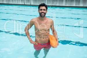 Man standing in swimming pool with rescue buoy