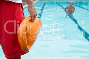 Lifeguard holding rescue buoy at poolside