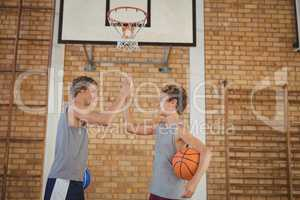 High school boys with basketball giving a high five