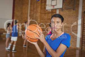 High school girl holding a basketball while team playing in background