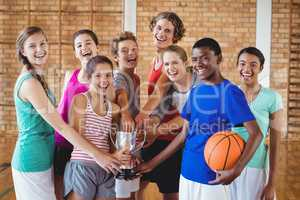 Smiling high school kids holding trophy in basketball court
