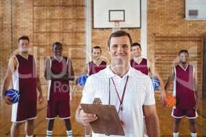 Smiling coach and basketball player standing in the court