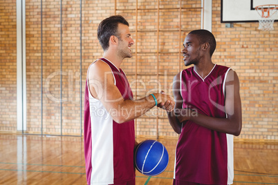 Basketball players shaking hands with each other in the court