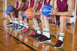 Basketball players sitting on bench with basketball