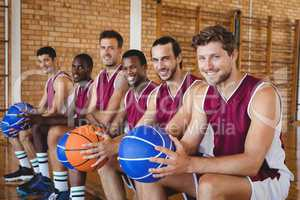 Smiling basketball players sitting on bench with basketball in the court