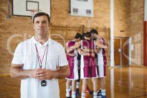 Confident coach standing in basketball court