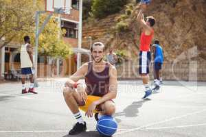 Basketball player with basketball sitting in basketball court
