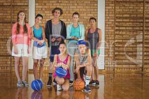 High school kids with basketball standing together in basketball court