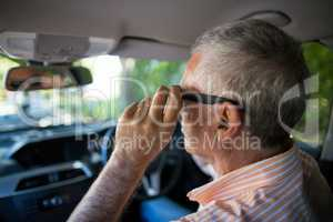 Senior man adjusting sunglasses in car