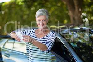 Senior woman holding phone while leaning on car door