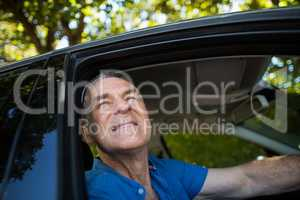 Thoughtful senior man sitting in car