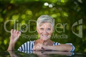 Senior woman holding eyeglasses by car