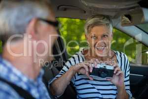 Senior woman photographing man in car