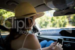 Young woman using phone in car