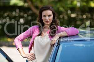 Confident young woman standing by car