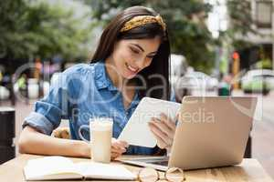Woman holding tablet while sitting at cafe
