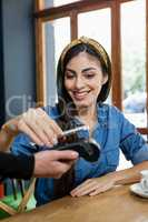 Woman making payment on credit card reader at cafe shop