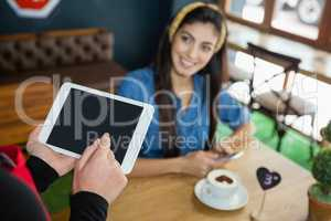 Cropped image of owner holding tablet while customer sitting at table