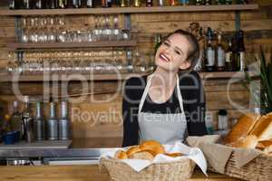 Portrait of cheerful owner standing by counter