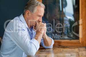 Thoughtful senior man sitting at table