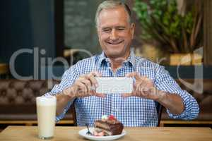 Smiling senior man photographing desert in plate at table