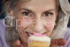 Close up portrait of woman holding cupcake
