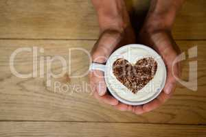 Person holding coffe cup with frothy art at wooden table
