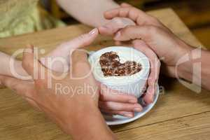 Cropped imageof couple hands around coffee cup
