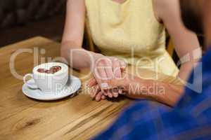 Close up of couple holding hands by coffee cup at table