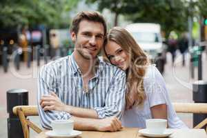 Portrait of smiling couple sitting at sidewalk cafe
