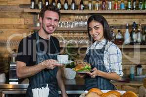Portrait of waiter and waitresses holding cup of coffee and food at counter