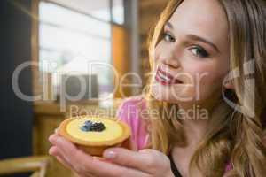 Portrait of beautiful woman holding cupcake