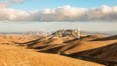 Timelapse clouds flying over dry mountains and smooth hills, Fuerteventura, Spain