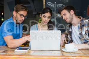 Friends using laptop while having coffee