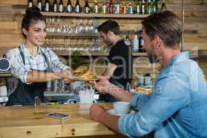 Waitress serving breakfast to man at counter