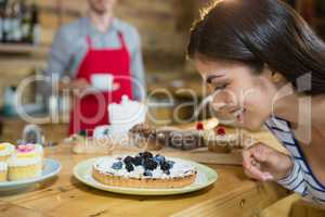 Woman looking at tart dish in caf�©