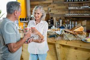 Senior couple interacting with each other while having coffee