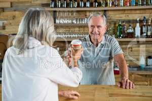 Senior man serving coffee to woman