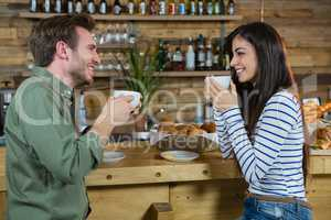 Couple interacting each other while having coffee at counter