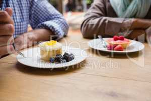 Senior couple having cupcake with blueberries and blackberries