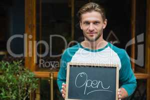 Portrait of smiling waiter holding chalkboard with open sign