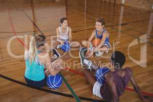 High school team relaxing in the basketball court