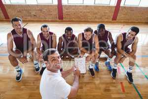 Smiling coach explaining game plan to basketball players