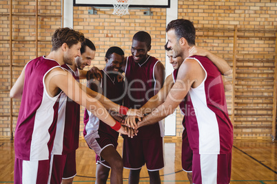 Team of basketball players stacking hands