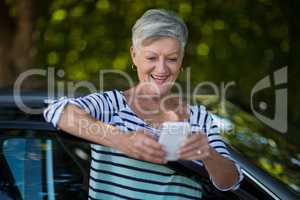 Senior woman using phone while leaning on car door