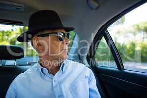 Senior man wearing sunglasses and hat in car