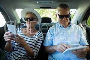 Senior couple using technologies in car