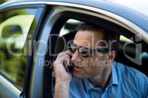 Young man talking on phone while driving car