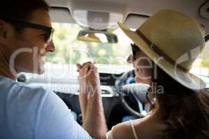 Happy couple holding hands while traveling in car